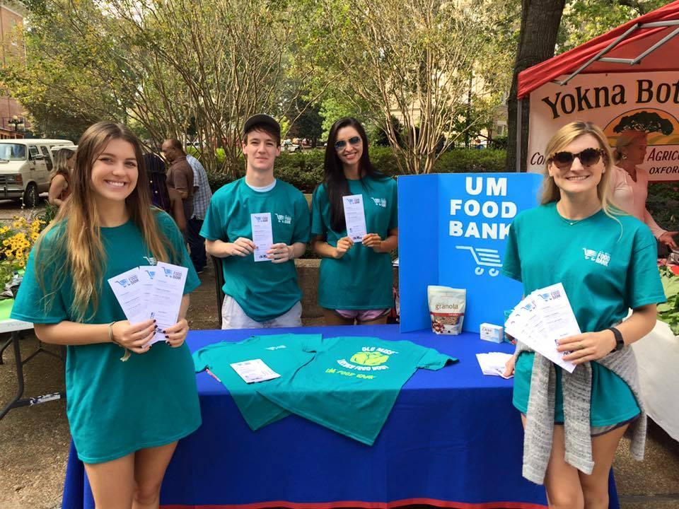 Four UM Volunteers holding up UM Food Bank Brochures at a UM Food Bank vendor table