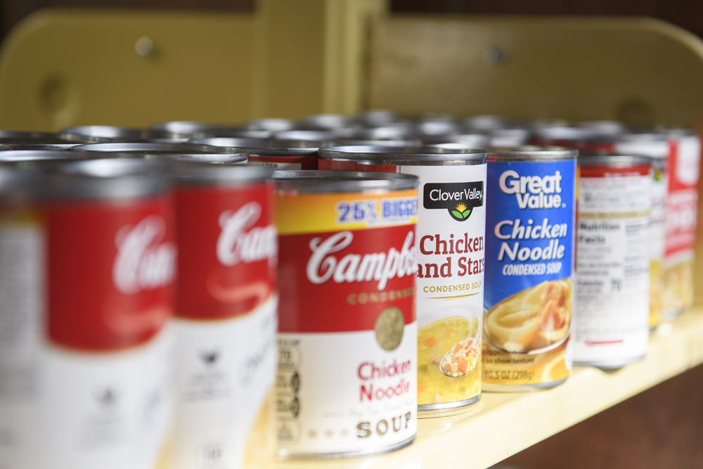 Cans of familiar brands of food on a shelf in a food pantry